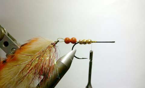 Add the rear hook and push the tungsten beads over the wire and stop just before the hook bend. Secure the beads with a couple of thread wraps.